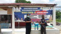 Anggota DPRK Aceh Besar Arfiansyah, S.Pd menyerahkan Masker yang diterima oleh aparatur gampong